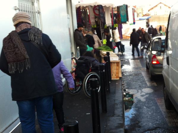 Une personne en fauteuil roulant coincée sur le trottoir un jour de marché.